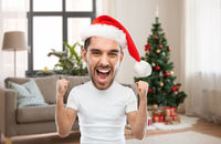 man in santa hat celebrating victory at home