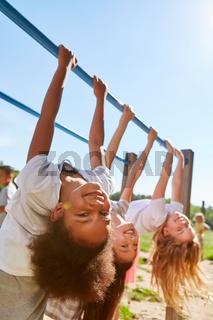 Mädchen turnen gemeinsam an Klettergerüst