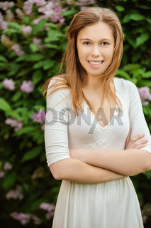 a beautiful young woman in a white dress amid a flowering tree