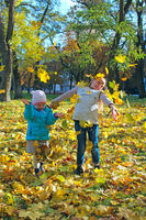 Young pretty sisters jump on yellow leaves in autumn park. Childs with autumn leaves. Little girls