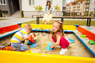 Little daughter and baby son playing together in modern sandbox