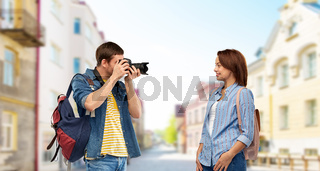 happy couple of tourists with backpacks and camera