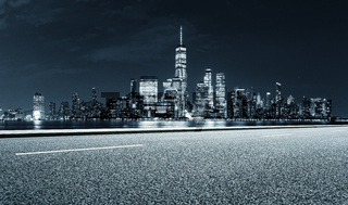 empty asphalt highway street with city skyline