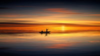 Two men fishing in a boat in lake during sunset. Geographical location: Europe