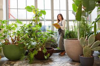 Junge Floristin im Treibhaus mit Checkliste