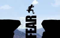 Man jumping over text FEAR in front of mountain background.