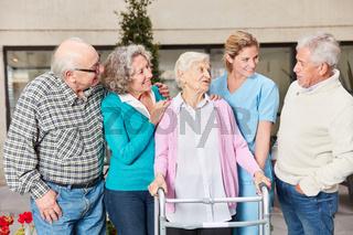 Gruppe Senioren im Gespräch mit Altenpflegerin
