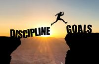 Man jumping over abyss with text DISCIPLINE/GOALS in front sunset.