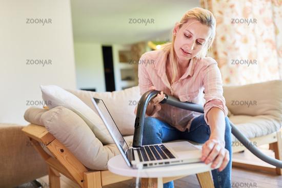 Putzfrau beim Staubsaugen an einem Laptop