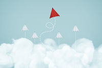 One unique red paper airplane lead the group of white paper airplane on blue sky and cloud  background . Business or design creative ideal leadership concept .