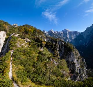 Sunny colorful autumn alpine scene. Peaceful rocky mountain view from hiking path near Almsee lake, Upper Austria.