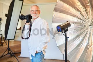 Cooler Fotograf mit digitaler Kamera vor Blitzanlage