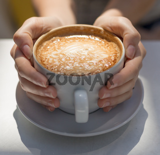 A woman's hands cupping a cappuccino with sunlight.