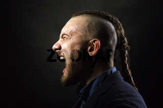 man with dreadlocks screams in a rage, looks like a viking, Iroquois haircut