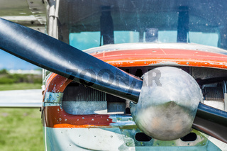 Small light utility aircraft, worn red and white paint, front view with propeller on sunny day.