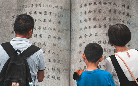 Family reading from a stone book