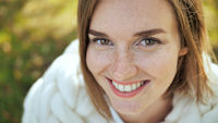 A smiling girl wrapped in a merino plaid in a city park in the early autumn. Face close-up.