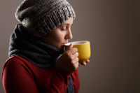 Young woman wearing a woolen scarf and a cap drinking hot tea. Autumn and winter season and illness concept.