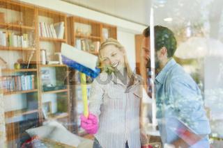 Junges Paar putzt zusammen Glas Fenster
