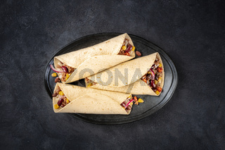 Burrito sandwich wraps, shot from the top on a black background. Tortillas stuffed with ground beef meat, rice, beans, onions, and chili peppers