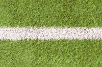 Artificial soccer field detail with a white line in the center