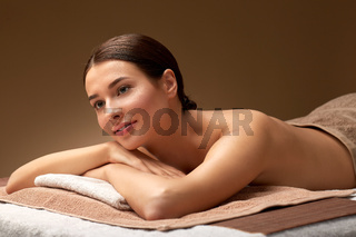 young woman lying at spa salon or massage parlor