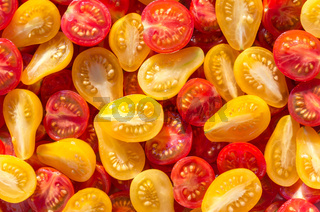 Fresh halves of Brazilian cherry tomatoes. Background of many colorful cherry tomatoes. Sliced yellow and red cherry tomatoes. Cherry tomatoes top view.