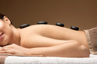 smiling woman having hot stone massage at spa