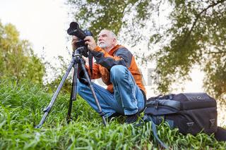 Senior als Naturfotograf mit Kamera und Stativ