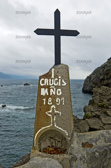 Black metallic cross on a rock above the Bay of Biscaya,islet of San Juan de Gaztelugatxe,Spain