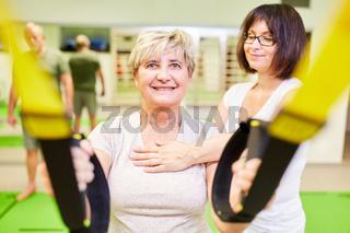 Seniorin beim Schlingentraining in der Physiotherapie