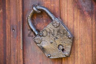 Old door lock. Old locked padlock with rings on old wooden board door.