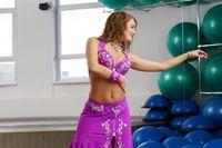 In gym. Beautiful belly dancer posing at camera