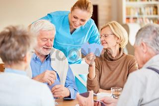 Altenpflegerin schaut zu beim Karten spielen