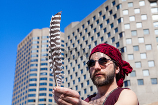 Spiritual man holds feather in city