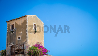 Sicily, Italy. Old house with purple flowers in Syracuse.