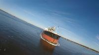 A Cargo Ship Steams Towards The Open Ocean Out Of A Harbor