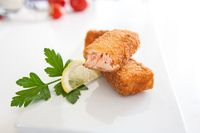 Fried salmon fish sticks with lemon and parsley on a white plate