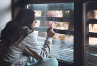 Young woman drawing a heart on the window