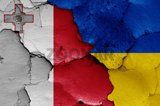 flags of Malta and Ukraine painted on cracked wall