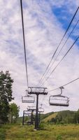 Vertical View of chairlifts against cloud covered blue sky during off season in Park City