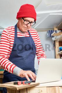 Elderly craftsman using laptop