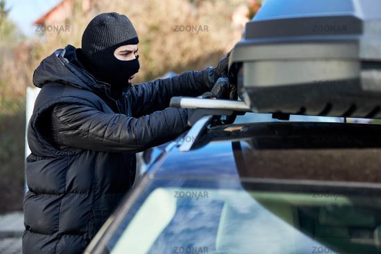 Dieb öffnet Dachbox auf Auto