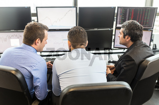 Business team brainstorming while checking data at computer screens.