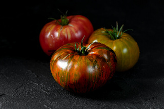 Heirloom tomatoes. Three tomatoes of different colors on a black textured background.