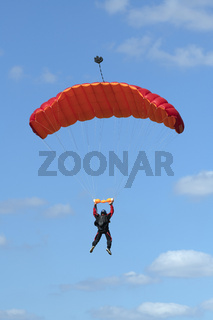 Parachutist floating to a square-shaped parachute