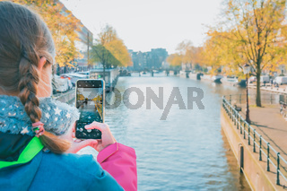 Young girl taking photo with smartphone of canal in Amsterdam