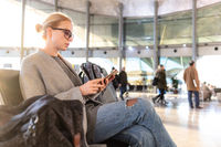 Female traveler using her cell phone while waiting to board a plane at departure gates at airport terminal.