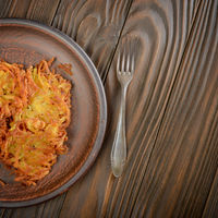 Top view of fresh homemade tasty potato pancakes in clay dish on wooden table
