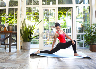 Young brunette woman in a sporty uniform doing yoga on the terrace of a house